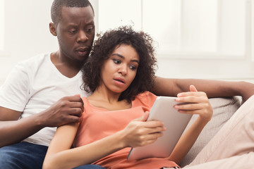 Black couple using digital tablet at home