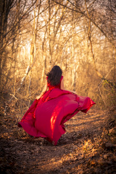 Girl in red dress running through woods