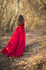 Girl in red dress waiting in woods