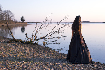 Girl in black dress by water