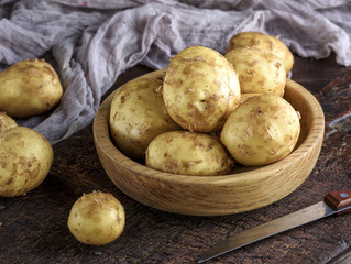 potatoes in the peel lay in a wooden bowl on a brown table