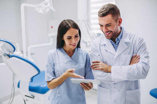 dentist and assistant looking at digital tablet screen