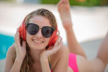 Smiling attractive blond curly hair woman wearing sunglasses lying on the floor and wearing headphone listen music from smart phone with enjoying on the summer day, relaxing time concept.
