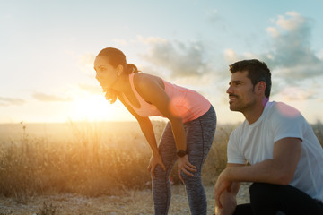 Running motivation and healthy fitness lifestyle. Couple of athletes resting during outdoor sunset workout.