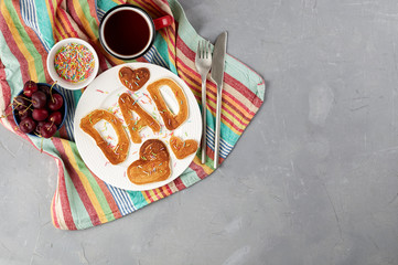 Special Father's Day breakfast. Alphabet Pancakes with sprinkles, cherries and cup of tea on a gray concrete background