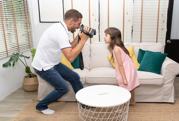 Funny Time!. Happy loving family and Father's Day.Cute little daughter and dad  playing making  a video camera at her home.