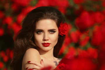 Outdoors portrait of Natural Beauty woman in red roses. Sensual female with rose flowers in hair. Sexy brunette with makeup over sunset blossom park. Passion and expression. Spanish flamenco style.