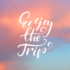 Enjoy the trip - handwritten lettering, summer holiday quote on abstract blur unfocused sky backdrop
