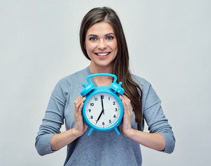 Young woman holding big blue alarm clock.