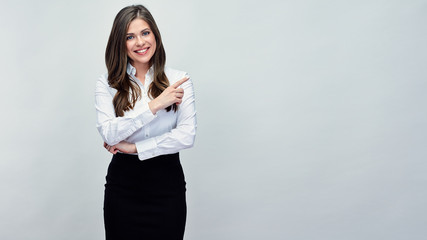 Smiling woman pointing with finger at copy space.