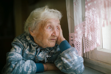 Elderly woman sitting at the table looking out the window.