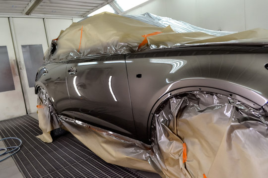 Painting the car in the workshop for body repair. Car covered with paper from hitting paint.