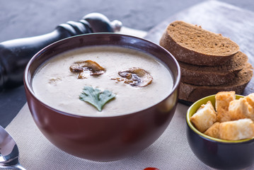 Mushroom cream soup in a brown plate on the table. Vegetarian traditional dish