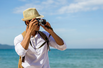 Young man taking photo with camera on the beach and blue sky in background, summer and vacation concept, copy space