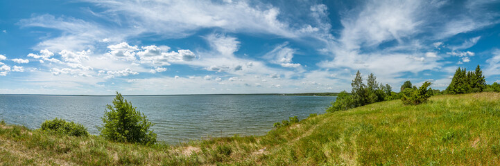 summer landscape. panoramic view of the lake under a beautiful cloudy sky with a coast in the foreground