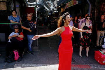 "A soloist from the Israeli Opera sings during an open rehearsal of Giacomo Puccini's ""Madama Butterfly"" at the Mahane Yehuda market in Jerusalem, ahead of the Israel Festival"