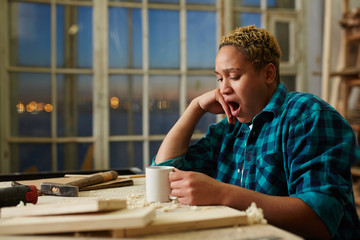 Exhausted female woodworker holding mug with hot drink and yawning while sitting near workbench in workshop in evening.