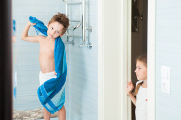 brother kid with towel and sister girl standing in door in bathroom in morning