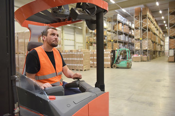 Workers in the warehouse of a forwarding company using forklifts for the transport and storage of goods for the trade  // Arbeiter im Warenlager einer Spedition mit Gabelstapler