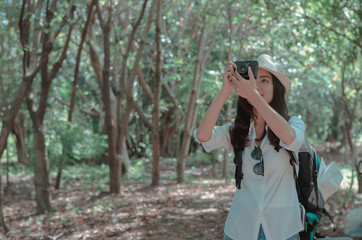 attractive woman adventure hiker go to trekking in the forest sightseeing natural at holiday travel concept. photographer using camera take a photo.