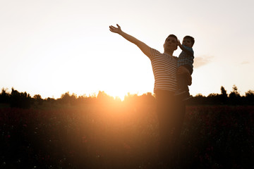 Father and son playing in field at the sunset time. Man holding little boy on hands and pointing to sky. Copy space for text