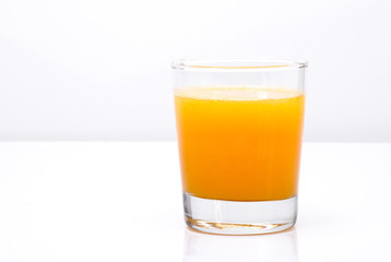 Fresh orange juice in the glass on an light background, horiizontal with place for a text.