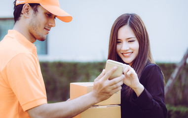 Delivery man is asking woman to sign mobile for the delivery