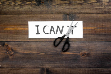 I can concept. Motivate youself, believe in yourself. Sciccors cut the letter t of written word I can't. Dark wooden background top view copy space
