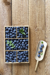 Fresh beautiful blueberries in wooden box on wooden table background. Top view
