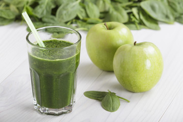 Spinach with apple juice a soft drink jar with straw on white wooden table