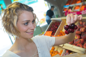 young woman buying cherries a weekly market