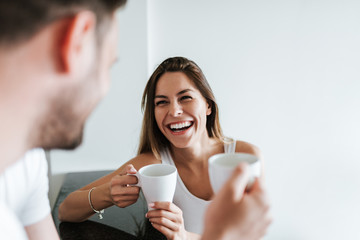 Laughing couple drinking coffee in the morning.