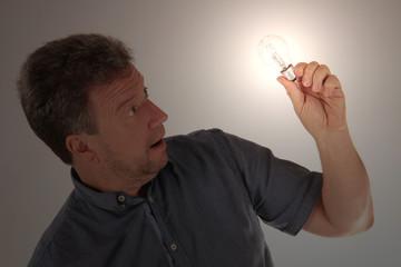 Mann betrachtet leuchtende Glühbirne
