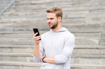 Man with beard walks with smartphone, urban background with stairs. Blogger use smartphone to stream video online. Man blogger using video conferencing on smartphone. Blogger concept