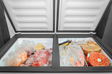 Frozen food in the freezer. Bagged frozen meat and other foods in a horizontal freezer with the two doors open. Food preservation.