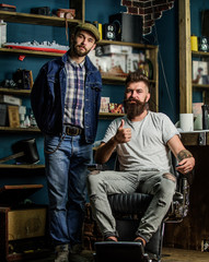 Hipster bearded client sits in hairdressers chair and shows thumb up. Client satisfied with service in barbershop. Hipster with haircut recommends professional barber service, salon on background