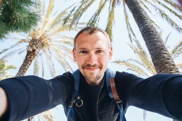 A young man tourist or blogger makes a selfie or reports to his subscribers on the background of palm trees in a hot country