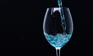 Wineglass filling with water with splashes on black background. Refreshing drink concept. Glass with blue water pouring with liquid with splashes and drops. Cocktail with blue liquid in glass