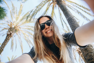 Young beautiful woman tourist or blogger makes a selfie or is reporting to its subscribers on the background of palm trees in a hot country