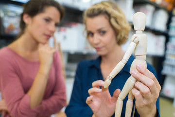 2 females looking at wooden figurine in store