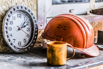 Lunch time at the production plant or a construction site for people who are working.  Still life clock showing the time lunch, an orange helmet, a dirty orange plastic Cup, close-up
