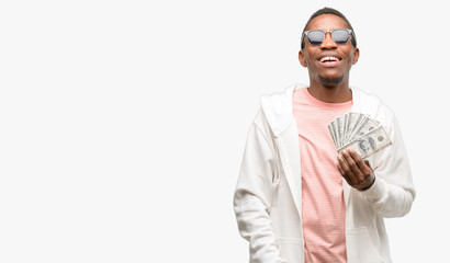 African man holding dollar bank notes thinking and looking up expressing doubt and wonder