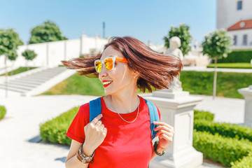 Happy young woman tourist walking and admiring view of a typical but wonderful flower garden in baroque style in Europe at sunny summer day. Travel destinations concept
