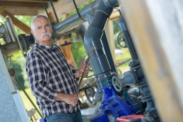 senior manual worker at a valve at plant