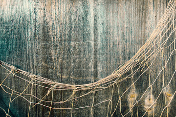 Fishing nets over wooden background with copy space. Fishing nets on wooden background. Hanging Fishnet on Wood Wall. Fishing net on vintage wood, maritime nautical background texture.