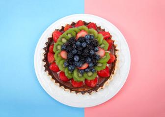 white porcelain plate with fresh summer fruit tart , strawberries, kiwis, blueberries, boysenberries, blackberries.  Top view flat lay on half blue half pink backgrounds