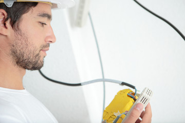 young electrician with test voltage screwdriver