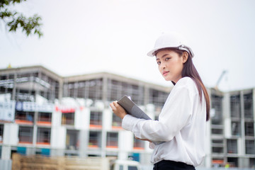 Female engineer inspecting construction work in hand holding clipboard with document.