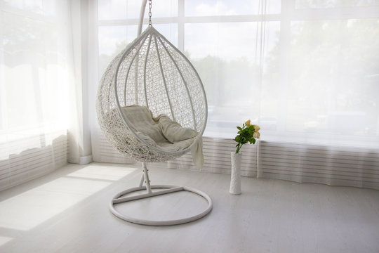 White interior. White hanging chair. Cocoon chair
