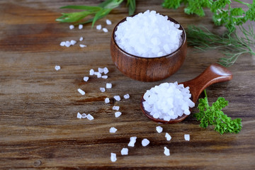 Big sea salt in a wooden bowl and spoon surrounded by herbs